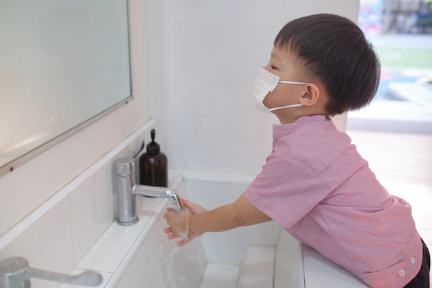 Asian 3 - 4 years old toddler boy child wearing protective medical mask washing hands by himself on sink in public toilet for kids, sanitation concept - soft & selective focus