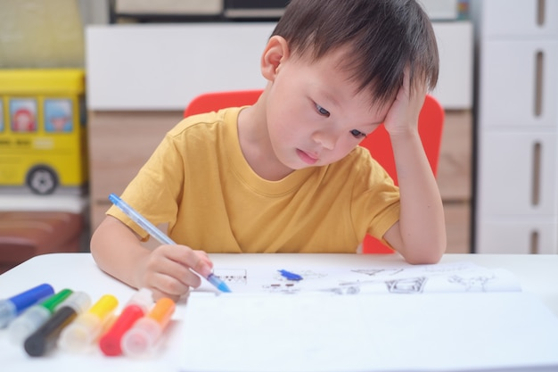 Asian 3 - 4 years old toddler boy child writing / drawing with pencil, student doing homework, little kid prepare for kindergarten test