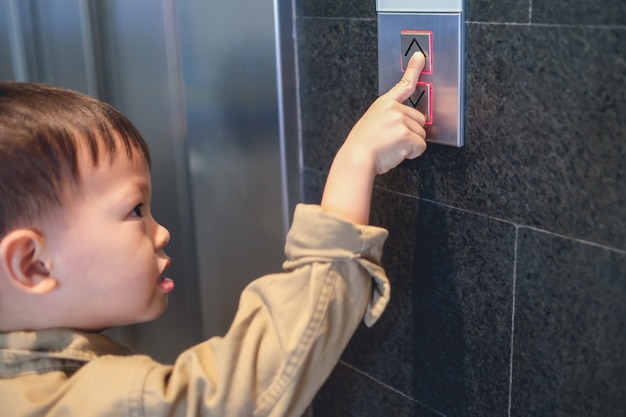 Asian 3 - 4 years old toddler boy kid standing in front of elevator trying to pressing lift / elevator button