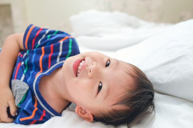 Asian 3 - 4 years toddler boy child waking up in bed, cheerful kid lying on bed looking at camera