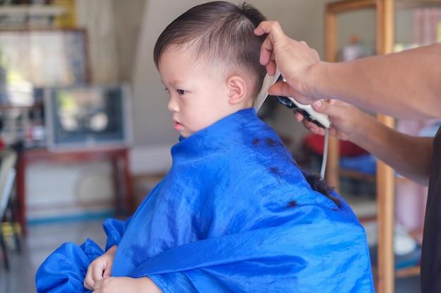 アジアの3歳の幼児男の子男の子美容院の理髪店で散髪を取得