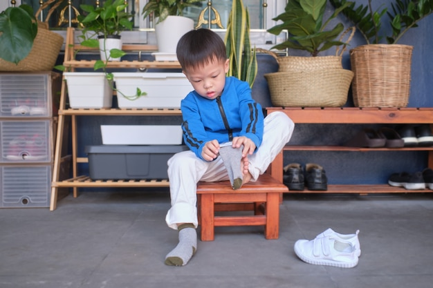 Asian 3 years old toddler kindergarten kid sitting near shoe rack near front door of his house and concentrate on putting on his own socks