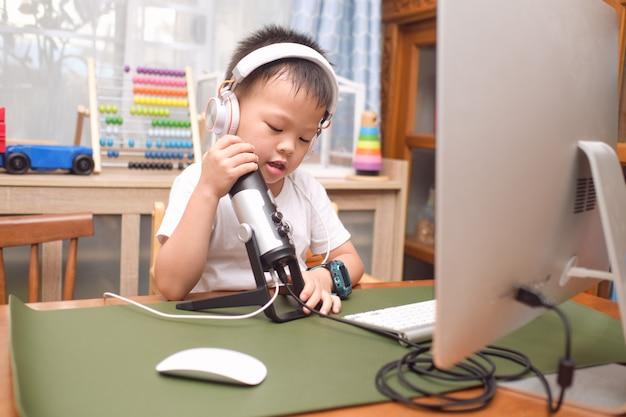 컴퓨터와 마이크를 사용하여 헤드폰을 착용 한 아시아 5 세 소년 아이가 집에서 친척에게 화상 통화를하거나 소셜 미디어 채널을위한 동영상 블로그를 만들 준비를합니다.