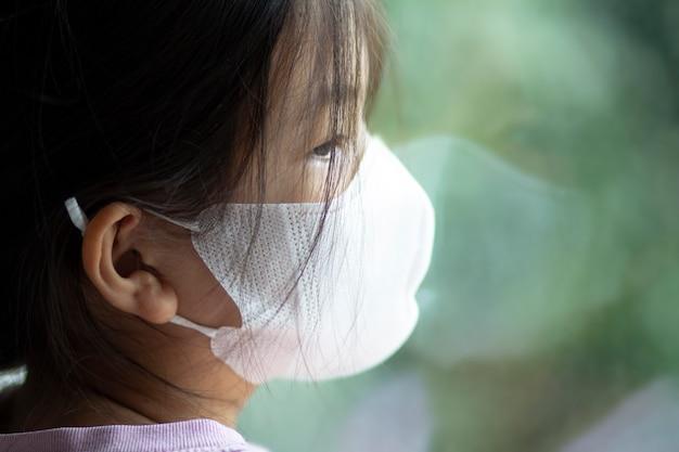 アジアの6歳または7歳の子供が医療用マスクを着用しています。窓際に立って外を見る少女。悲しげで退屈そうに見えます。