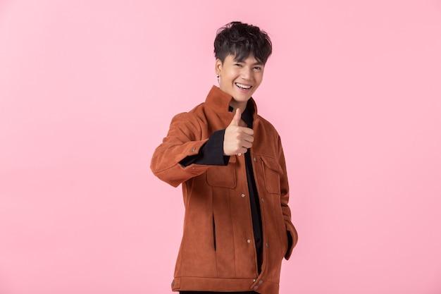 손으로 가리키는 잘생긴 젊은 아시아 남자는 분홍색 공백 복사 공간 스튜디오 배경에서 격리된 사랑에 빠진 카메라를 바라보는 측면 눈까지 엄지손가락을 보여줍니다.