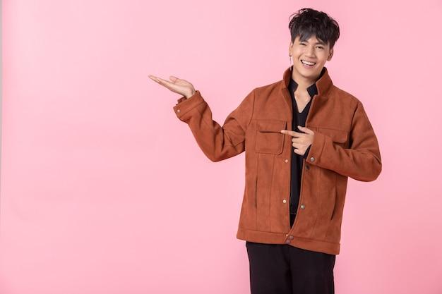 분홍색 공백 복사 공간 스튜디오 배경에서 격리된 사랑에 빠진 카메라를 바라보는 옆 눈을 두 손과 손가락으로 가리키는 아시아 남자.