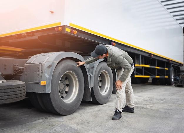 Азиатский водитель грузовика проверяет колеса и шины прицепа, техническое обслуживание и безопасность