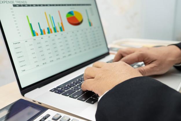 아시아 회계사 유형 키보드는 현대 사무실, 금융 및 비즈니스 개념에서 노트북으로 정보, 작업, 계산 및 분석 보고서 차트 그래프 프로젝트 회계를 입력합니다.