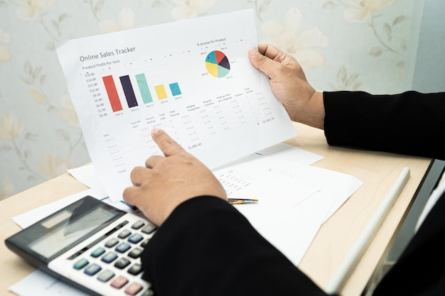 Asian accountant working and analyzing financial reports project accounting with chart graph and calculator in modern office, finance and business concept.