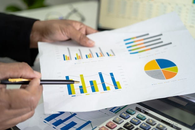 Asian accountant working and analyzing financial reports project accounting with chart