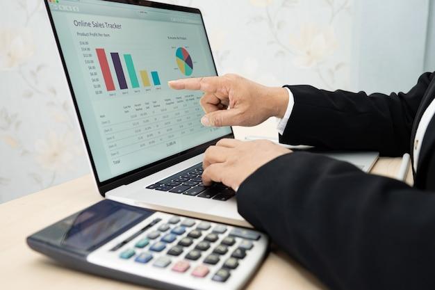 Азиатский бухгалтер, работающий и анализирующий финансовые отчеты, бухгалтерский учет проекта с диаграммой и калькулятором