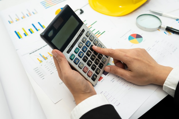 Азиатский бухгалтер работает и анализирует финансовые отчеты проекта.