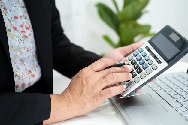 財務報告プロジェクトの作業と分析を行うアジアの会計士
