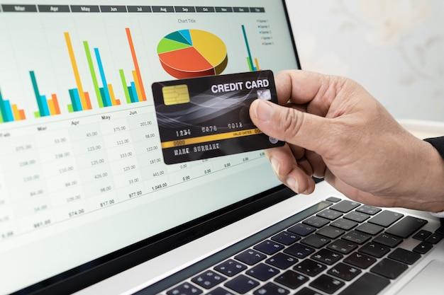 アジアの会計士は、現代のオフィス、金融、ビジネスの概念でノートブックとクレジットカードを使用してレポートプロジェクトの会計を計算および分析します。