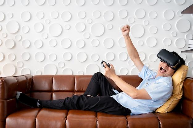 リビングルームで仮想現実ゴーグル(vr)を使用してビデオゲームをプレイするアジアの成人男性。