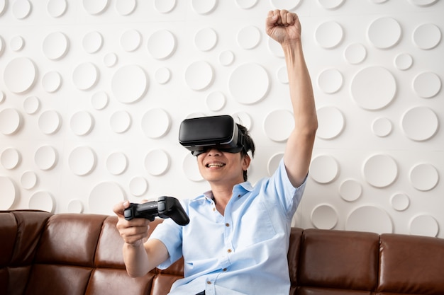 Asian adult man playing video game by using virtual reality goggles in the living room
