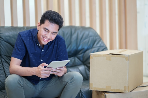 Asian adult man using tablet device for checking inventory stock of boxes