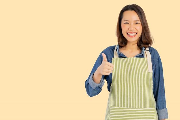 アジアの大人の女性(主婦)エプロンを着用し、背景に分離された最高の親指