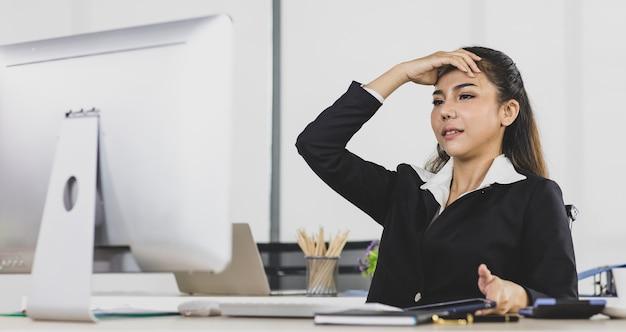 Азиатская взрослая женщина - офисные люди, серьезно сидящие за рабочим столом, выглядят разочарованными работой.
