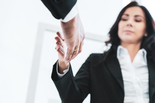アジア人と白人の民族ビジネスマンは、商談を終えて完了した後、一緒に握手をします。ビジネスパートナーシップと同僚への信頼。ビジネスコンセプトで成功。