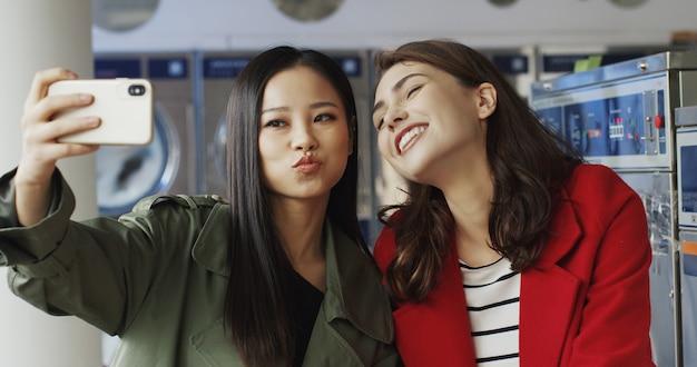 ランドリーサービスでselfie写真を撮りながら笑顔とスマートフォンのカメラにポーズをとってアジアと白人の若い美しい女の子。洗濯機で携帯電話で自分撮り写真を作るきれいな女性。