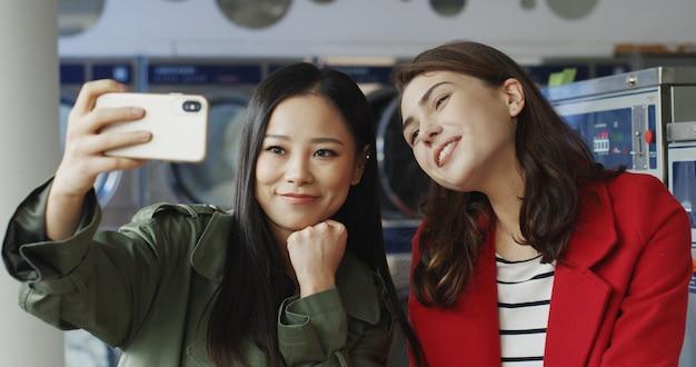 Азиатские и кавказские молодые красивые девушки усмехаясь и представляя к камере smartphone пока делающ фото selfie в прачечной. милые женщины делая фото selfies с телефоном на стиральных машинах.