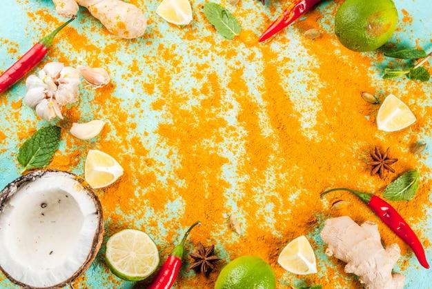 アジア料理とタイ料理、料理の背景。スパイスと材料-ココナッツ、生inger、赤唐辛子、ライム、カレー、ミント、スパイス。明るい青の背景。トップビューコピースペース