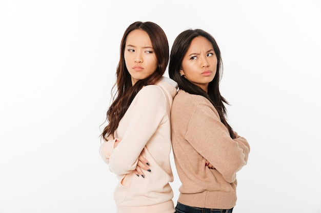 Asian angry ladies sisters standing isolated