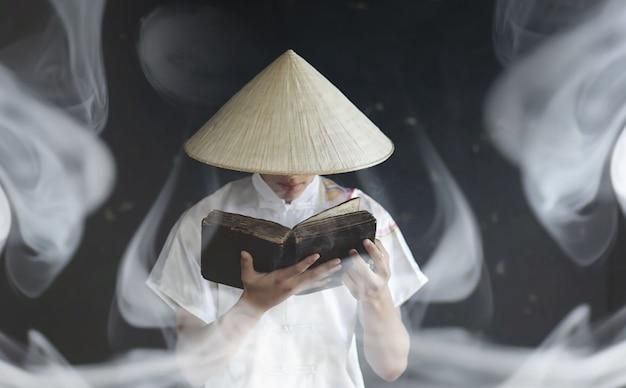 着物姿のアジア人出演青年が本で祈る