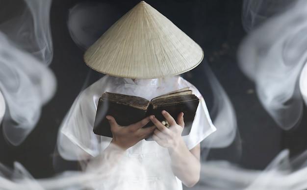 Молодой человек азиатской внешности в кимоно молится с книгой