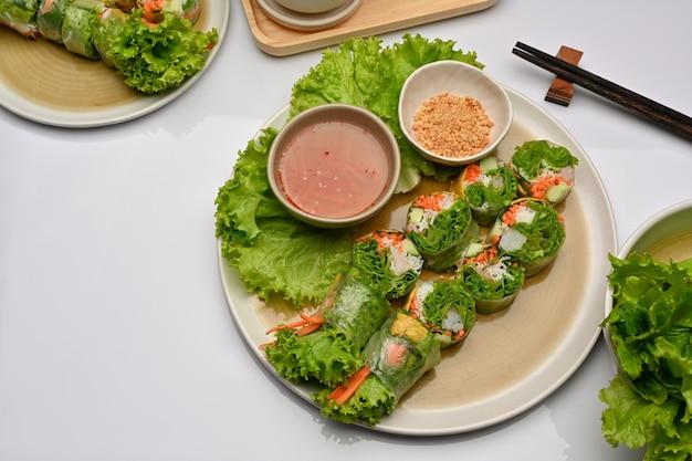 Азиатская закуска вьетнамские спринг-роллы, поданные с соусом для макания на обеденном столе