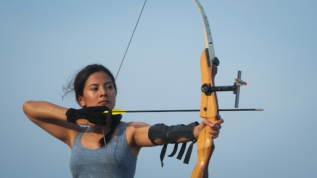 Asian archery woman with bow shooting on the beach