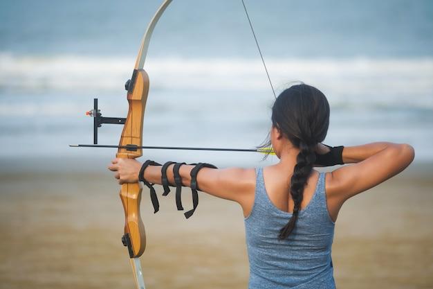 Азиатская стрельба из лука женщина со стрельбой из лука на пляже