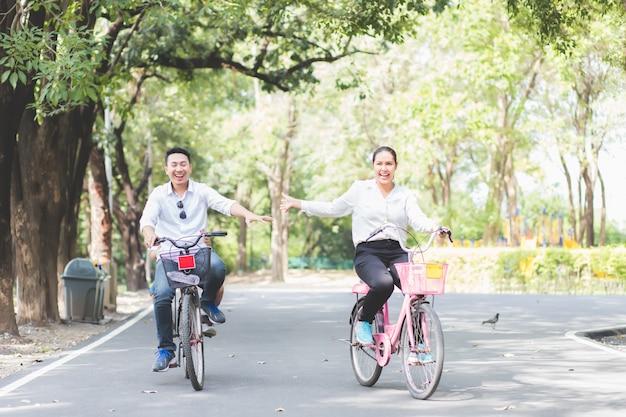 アジアのアジアのカップルは庭で自転車に乗って楽しく週末に楽しんでいます。
