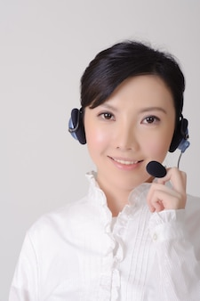 笑顔であなたを見ているアジアのアシスタントの女性、灰色の壁にクローズアップの肖像画。