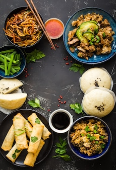 Asian assorted food set, dark rustic stone background. chinese dishes.