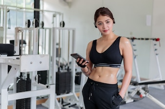 Asian athlete in sportswear fashion clothing. Sportswoman listening to music using phone app for fit