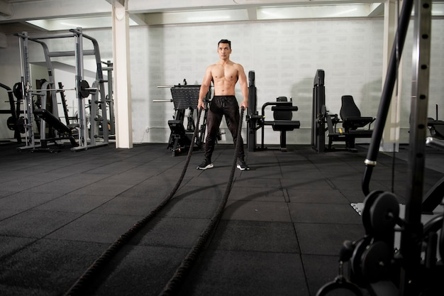 Asian athletic man with rope doing exercise in fitness gym