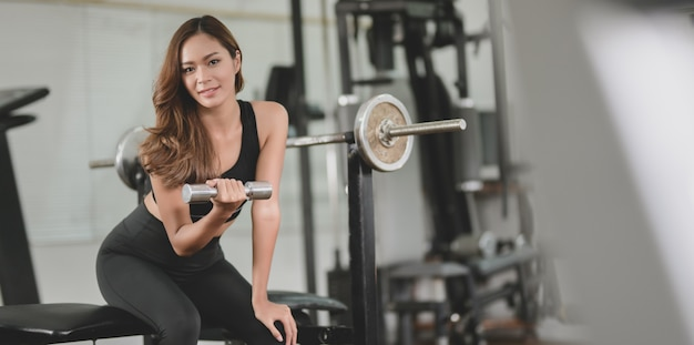Asian athletic woman holding dumbbell and smiling at the camera