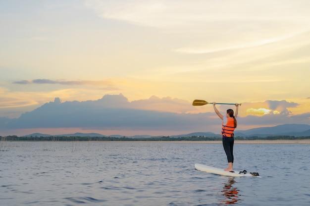 湖のスタンドアップパドルボードでアジアの運動女性。夏休みのソロアウトドアsupアクティビティとウォータースポーツ。