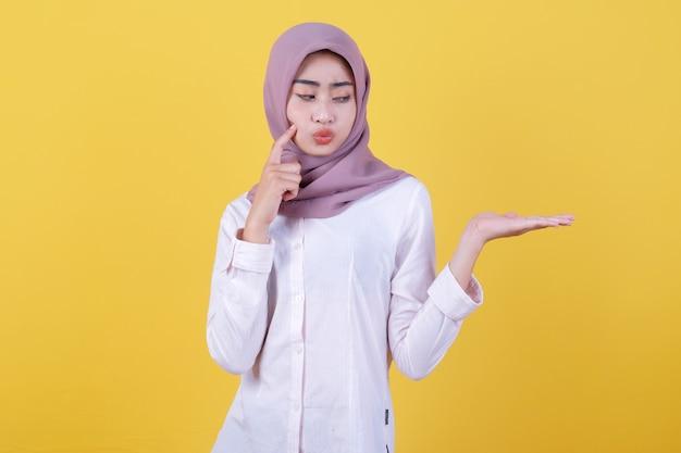 Азиатская привлекательная девушка показывает что-то под рукой в хиджабе, думая что-то жестом