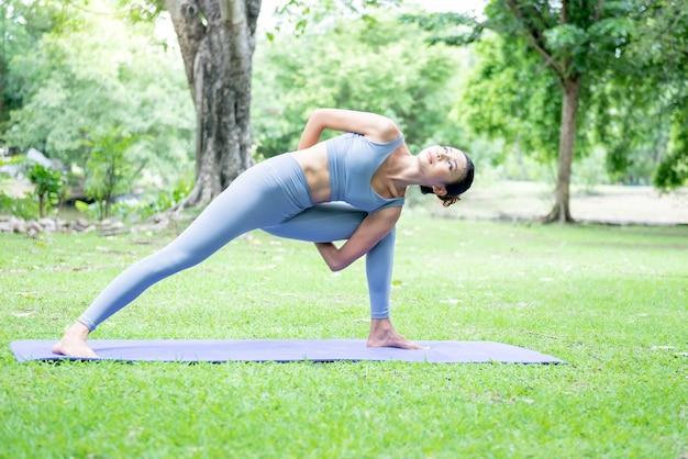 緑豊かな公園で優雅な姿勢でヨガをしているアジアの魅力的な女性。