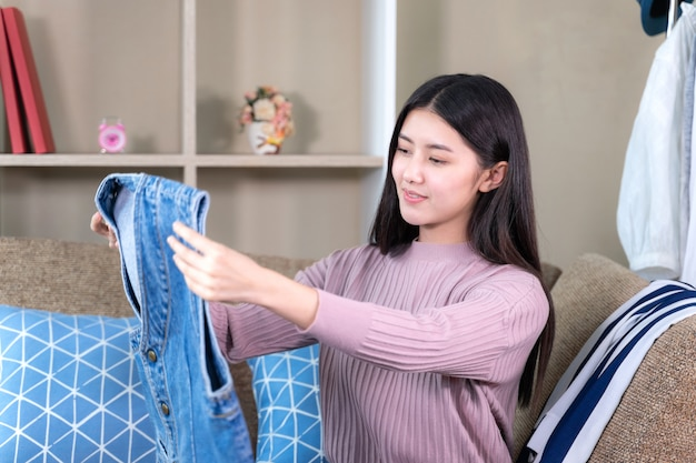 Asian attractive woman looking to new clothes with smiling