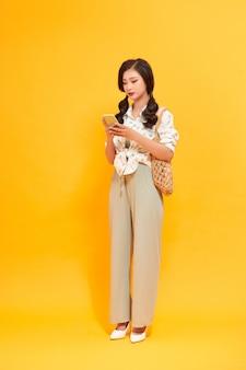 Азиатская привлекательная женщина с помощью смартфона и переноски коричневой корзины.