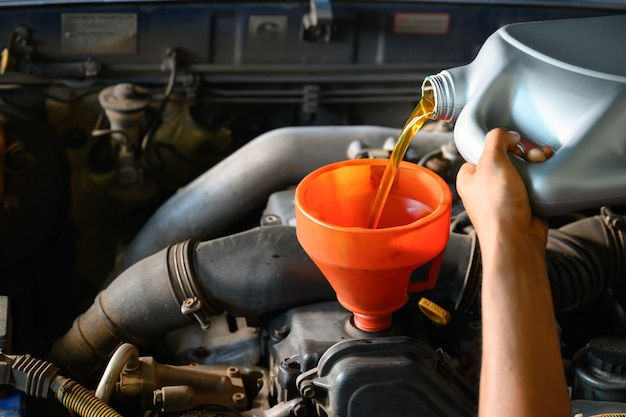 Asian auto mechanic working in auto repair shop pour oil for oil change in the garage for customers who repair cars and change oil.