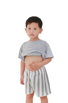 Азиатский мальчик в возрасте около 3 лет снимает рубашку, демонстрируя свой большой животик