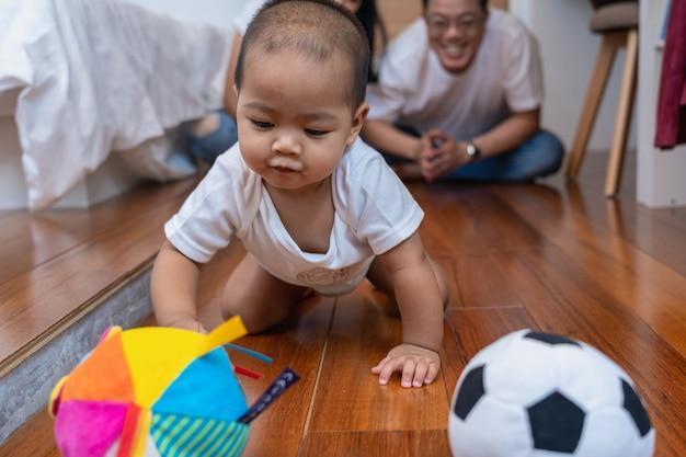 アジアの赤ちゃんがクロールし、木製の床にボールを演奏