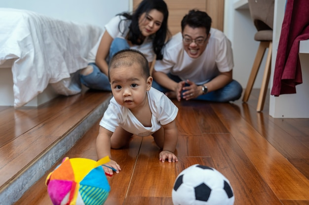 Asian baby boy crawl and playing the ball on the wooden floor