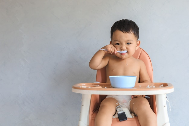 Asian baby boy eating food by himself