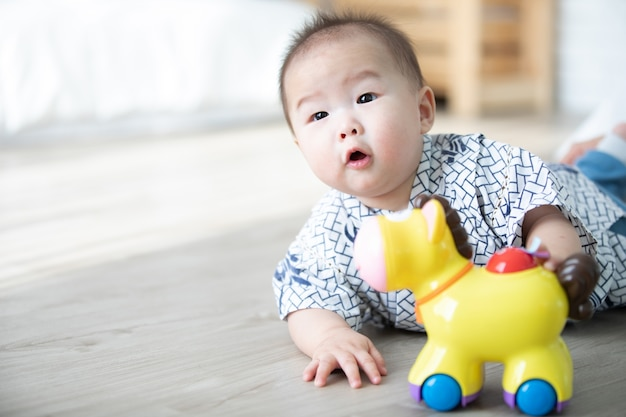 Asian baby boy playing hourse toys on the floor